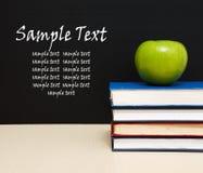 Schulebücher mit Apfel auf Schreibtisch Lizenzfreie Stockfotos