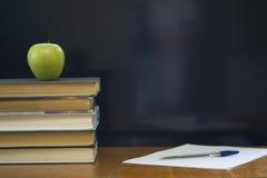 Schulebücher mit grünem Apfel auf Schreibtisch. Lizenzfreie Stockfotos