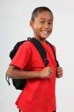 Schulejunge 9, der rotes und glückliches Lächeln im Studio trägt Stockfoto
