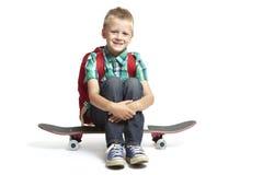 Schulejunge, der auf einem Skateboard sitzt stockbild