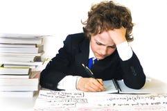 Schulejunge, der schwer arbeitet Stockbilder