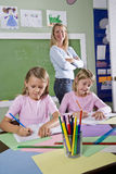 Schulemädchen, die in Notizbücher mit Lehrer schreiben Stockbild