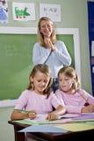Schulemädchen, die in Notizbücher mit Lehrer schreiben Lizenzfreies Stockfoto
