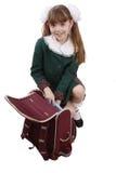 Schulemädchen packt herauf Rucksack. Lizenzfreie Stockfotografie
