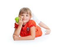Schulemädchenportrait, das den grünen Apfel getrennt isst Lizenzfreie Stockfotos