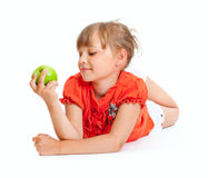 Schulemädchenportrait, das den grünen Apfel getrennt isst Stockfoto