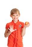 Schulemädchenportrait, das den roten Apfel getrennt isst Lizenzfreies Stockfoto