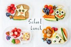 Schulen Sie Brotdosen für Kinder mit Lebensmittel in Form von lustigen Gesichtern Lizenzfreie Stockbilder