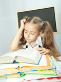 Schulen Sie das Mädchen, das Heimarbeit hinter Stapel Büchern bildet. Stockbild