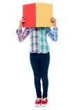 Schulen Sie das Mädchen, das ihr Gesicht hinter einem Notizbuch versteckt Stockbild