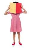 Schulen Sie das Mädchen, das ihr Gesicht mit einem Buch versteckt Stockbild
