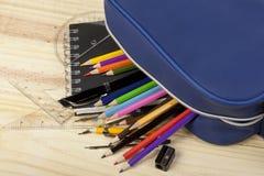 Schulen Sie den Bleistiftkasten, der heraus auf hölzernen Klassenzimmerschreibtisch verschüttet wird Stockfotos