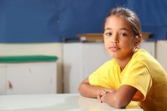 Schulen Sie die Arme des Mädchens 10, die an ihrem Klassenzimmerschreibtisch gefaltet werden Lizenzfreie Stockfotografie