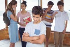 Schulen Sie die Freunde, die einen traurigen Jungen im Korridor einschüchtern lizenzfreies stockbild