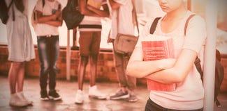 Schulen Sie die Freunde, die ein trauriges Mädchen im Korridor einschüchtern stockbilder