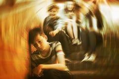 Schulen Sie die Freunde, die einen traurigen Jungen im Schulkorridor einschüchtern lizenzfreie stockfotografie