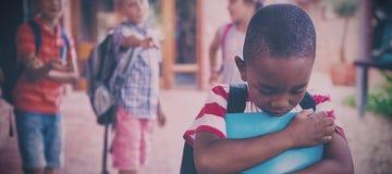 Schulen Sie die Freunde, die einen traurigen Jungen im Schulkorridor einschüchtern lizenzfreies stockbild