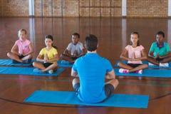 Schulen Sie die Kinder und Lehrer, die während der Yogaklasse meditieren stockbilder