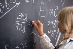 Schulen Sie Mädchenschreiben auf Tafel Lizenzfreies Stockfoto