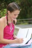 Schulen Sie Mädchenschreiben im Notizbuch draußen Stockbild