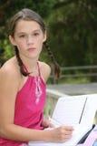 Schulen Sie Mädchenschreiben im Notizbuch draußen Stockbilder