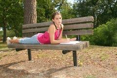 Schulen Sie Mädchenschreiben im Notizbuch draußen Lizenzfreies Stockbild
