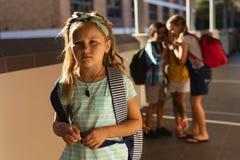 Schulfreunde, die ein trauriges Mädchen in der Halle der Volksschule einschüchtern lizenzfreies stockfoto