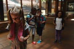 Schulfreunde, die ein trauriges Mädchen im Korridor der Volksschule einschüchtern lizenzfreies stockbild