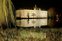 Schulgebäude im Spiegel von Teich bis zum Nacht in Litovel Lizenzfreies Stockbild