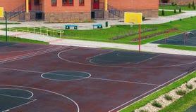 Schulhof mit einem Spielplatz für Basketball stockfotos