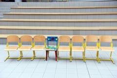 Schulholzstühle in Folge mit einem färbten den Stuhl, der heraus haftet Lizenzfreie Stockfotos