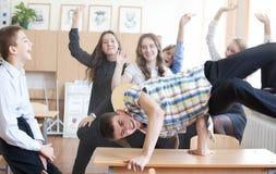 Schuljunge, der hinteren leichten Schlag auf dem Schreibtisch im Klassenzimmer tut sonnig stockfotos