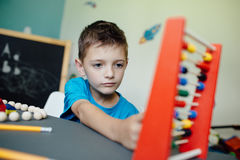 Schuljunge, der Mathe mit einem Abakus lernt Stockfotos