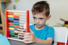 Schuljunge, der Mathe mit einem Abakus lernt Lizenzfreie Stockfotografie