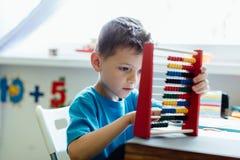 Schuljunge, der Mathe mit einem Abakus lernt Stockbild