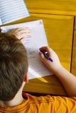 Schuljunge, der seine Hausarbeit schreibt Lizenzfreies Stockfoto