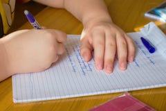 Schuljunge, der seine Hausarbeit schreibt Lizenzfreies Stockbild