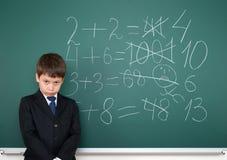 Schuljunge entscheidet Beispielmathe, das auf Tafelhintergrund, Bildungskonzept falsch ist lizenzfreie stockfotos