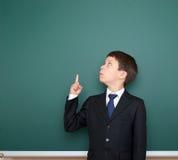 Schuljunge im schwarzen Anzugsshowfinger herauf Geste und Wunder, Punkt auf grünem Tafelhintergrund, Bildungskonzept Lizenzfreie Stockfotografie