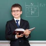 Schuljunge mit Buch, Archimedes-Prinzipzeichnung auf dem Tafelhintergrund, gekleidet im klassischen schwarzen Anzug, Bildungskonz Lizenzfreie Stockfotografie