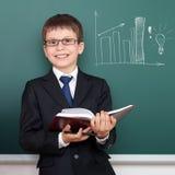 Schuljunge mit Buch, Balkendiagrammzeichnung auf Tafelhintergrund, kleidete im klassischen schwarzen Anzug, Bildungskonzept an Stockbilder