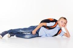Schuljunge mit der Tasche, die auf dem Boden liegt Lizenzfreie Stockfotos