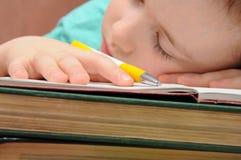 Schuljunge schläft mit einem Buch Stockbilder