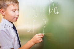 Schuljunge schreibt englisches Alphabet mit Kreide auf Tafel Stockbilder