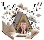 Schuljungen-Lesebuch mit Buchstaben Stockfotografie