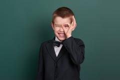 Schuljungen-Show-O.K.zeichen, Porträt nahe grünem leerem Tafelhintergrund, kleidete im klassischen schwarzen Anzug, ein Schüler a Lizenzfreie Stockbilder