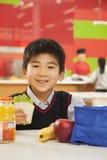 Schuljungenporträt, welches das Mittagessen in der Schulcafeteria isst Lizenzfreie Stockfotos