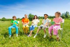Schulkameradgriff-Übungsbücher, die draußen sitzen Stockfotos