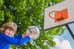 Schulkind, das Ball auf Brett mit Korb abzielt Lizenzfreies Stockbild