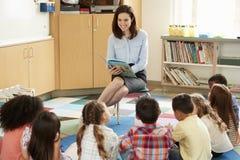 Schulkinder, die auf dem Boden hört auf den Lehrer gelesen sitzen lizenzfreie stockbilder